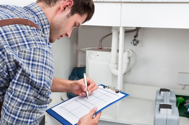 A public adjuster inspecting sink pipes